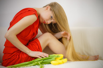 Sad elegant woman sitting on sofa with tulip