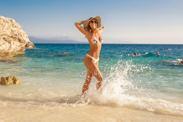 Beautiful young woman with a hat walking on the beach in the water