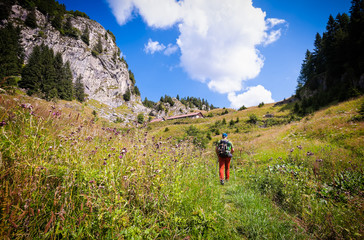 Man hiking on mountains over the trail between meadows