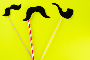Happy fathers day, birthday party,Purim, Halloween concept. Black paper mustache and smoking pipe with copy space for text on yellow background.Top view.