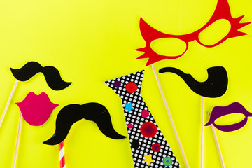 Top view image of  funny masks beard, glasses, mustache,lips ,smoking pipe and tie on yellow background. Party, birthday, Halloween Father day, Purim, Fool day concept.