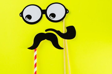Top view image of  funny masks glasses, smoking pipe and mustache on yellow background. Party, birthday, Halloween Father day, Purim, Fool day concept.