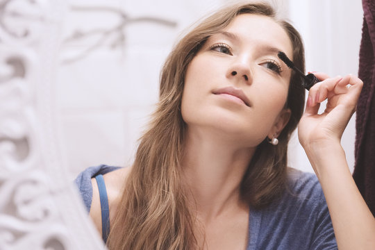 Young woman dyes her eyelashes with mascara brush. Young beautiful woman applying mascara makeup on eyes at bathroom.