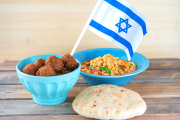 Israel flag, Falafel balls in a bowl, pita bread and hummus topped chickpea seeds in a dish on wooden  background. Falafel,hummus and pita Traditional Israeli healthy vegan food.