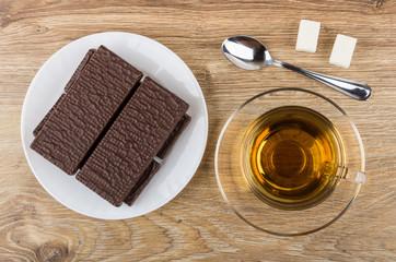 Wafer in chocolate, tea on saucer, sugar, teaspoon on table