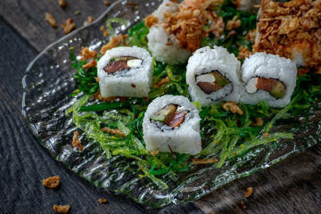 sushi with tuna and shrimp on green seaweed salad bed