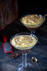 vanilla and chocolate pudding in tall glass with grated chocolate pieces