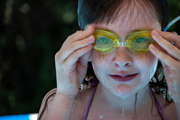 young girl in yellow swim goggles pool