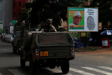 A convoy of peace-keeping forces passes next to an electoral billboard of Ibrahim Boubacar Keita, President of Mali and candidate for Rally for Mali party (RPM) during a patrol in Bamako