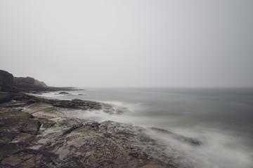 long exposure shot of Waves crashing against rocks on the coastline