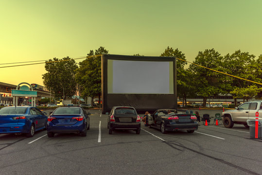Spectators at a car parking lot with cars, an inflatable screen of the summer cinema, waiting for a movie