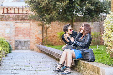 two  women using smart phone in the city