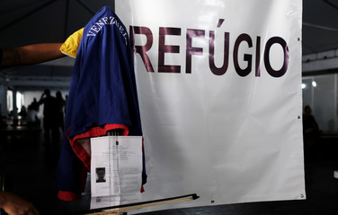 Dulce from Venezuela poses with her instrument and her refugee status document, through the Federal Police and the United Nations High Commissioner for Refugees (UNHCR) at the Pacaraima border control