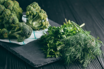 On a dark wooden table, fresh green broccoli, parsley, dill for your health. Flatlay. Recipe. Ingredients. Dietary food. Place under the text.