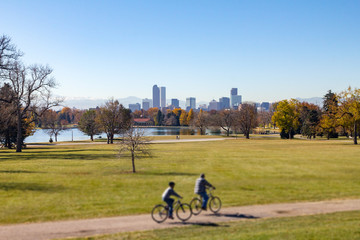 Denver Colorado downtown skyline with people riding bicycles on a trail through City Park and snow capped mountains in the background