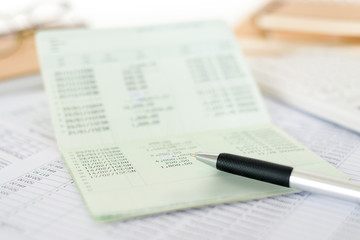 Close up of saving account passbook with pen and statement. Business and financial analysis concepts.