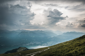 View from top of a mountain in austria with clouds on the sky and mountains and a lake in the valley