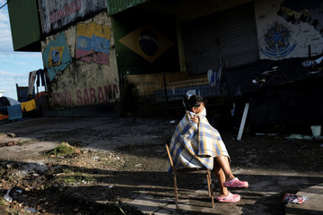 Venezuelan woman sits on a chairalong the street after showing her passport or identity card at the Pacaraima border control