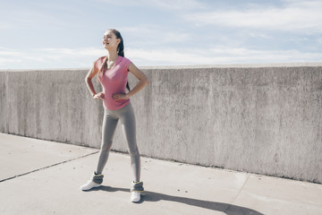 active slender girl warms up before training on the outdoor air, leads a healthy lifestyle