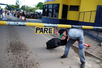 Venezuelan man carries his luggage after showing his passport or identity card at the Pacaraima border control