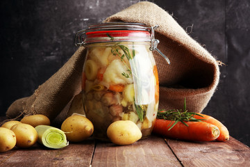 Jar with variety of pickled vegetables. Broth, Carrots, field garlic, parsley in glas. Preserved food