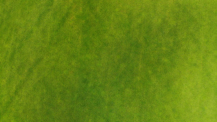 Beautiful trimmed green grass texture background. Golf course or football from a bird's eye view.