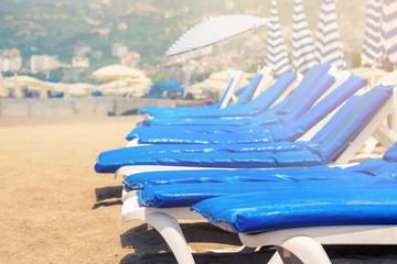Empty sunbeds with blue mattresses on sandy beach