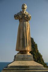 Betende Statue vor blauem Himmel in goldenem Licht