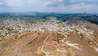 Aerial birds eye view drone photo ancient Archangelos scenic old town with castle on Rhodes island, Dodecanese, Greece. Beautiful picturesque white houses. Famous tourist destination in South Europe