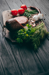 Smoked salami on a black table and a brown board. Sausages with rosemary, garlic and pepper and tomato cherry, dill, parsley.