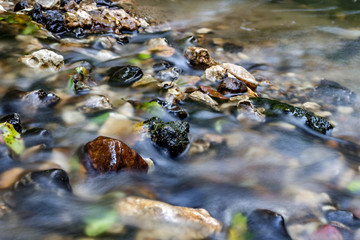 A stony streambed, a stream of clear water. Stream Repinka in the city of Obninsk, Russia