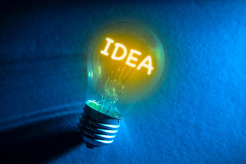 Light bulb filament word IDEA on blue