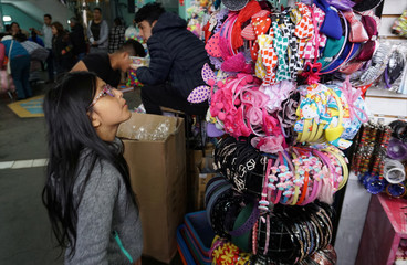 A child looks at hairbands imported from China at Central Market in Lima