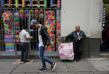 A man walks near a store that sells toys and products imported from China at Central Market in Lima