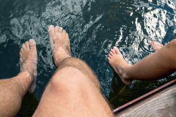 Two pairs of legs in the river.
