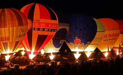 Balloons are illuminated by their burners during the 'Night Glow' display at the Bristol International balloon fiesta in south west England