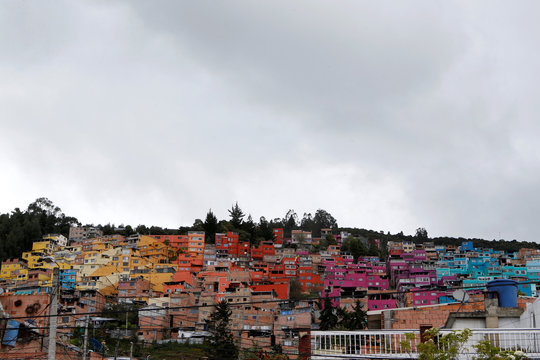 "An overview of the Buenavista neighborhood after residents there painted the exterior of their houses to form the largest macromural in Colombia called ""Sol Lunar"" in Bogota"