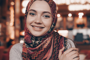 beautiful an Arabian girl with a headscarf on her head posing in a cafe, looking at the camera and smiling, waiting for her food