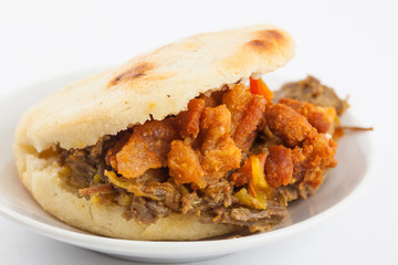 Arepas filled with shredded beef and pork rind served in white dish on white background