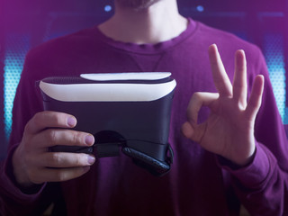 close up person holds the virtual reality glass in fron of chess with okay sign