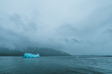 Iceberg in foggy and stormy water