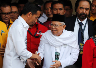 Indonesian President Joko Widodo (L) shakes hands with his vice-presidential running mate for the 2019 elections Islamic cleric Ma'ruf Amin while greeting supporters in Jakarta