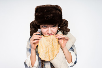 funny Russian girl in a black fur hat eats hot pancakes, celebrates Shrovetide
