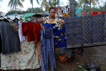 Villagers dry their clothes at a refugee camp after an earthquake hit Sigar Penjalin village in North Lombok
