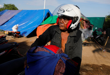 A villager carries clothes at a refugee camp after an earthquake hit Sigar Penjalin village in North Lombok