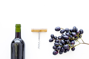 Red wine concept. Glass bottle with beverage near bunch of grapes and corkscrew on white background top view space for text Fototapete