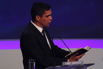 Presidential candidate Daciolo of Patriots reads the Bible during the first television debate at the Bandeirantes TV studio in Sao Paulo
