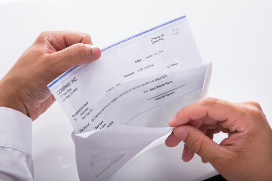 Businessman opening envelope with paycheck