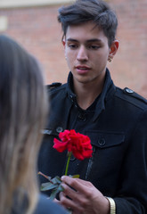 Handsome young man gives flower to woman