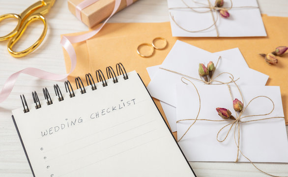 Flat lay and close up view of checklist and wedding invitations on a white wooden tabletop, blank space.